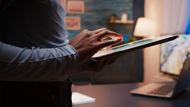 夜遅くにリビングルームに立っているタブレットコンピューターを持っている黒い女性の手のクローズアップ写真。仕事のために残業しているソーシャルネットワーク、テキストメッセージ、ブログを使用しているアフリカ系アメリカ人の女性