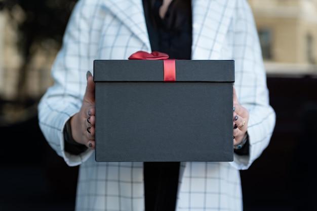 여성 손에 검은 선물 상자의 사진을 닫습니다. 그녀의 손에 아름 다운 선물 상자를 들고 소녀입니다. 공간을 복사합니다.