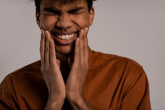 Крупным планом фото темнокожего мужчины выглядит так, будто у него болят зубы. мужчина носит рубашку, изолированный серый цвет фона.