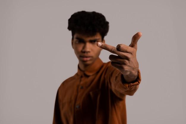 Крупным планом фото темнокожего человека показывает средний палец прямо в камеру. мужчина носит рубашку, изолированный серый цвет фона.