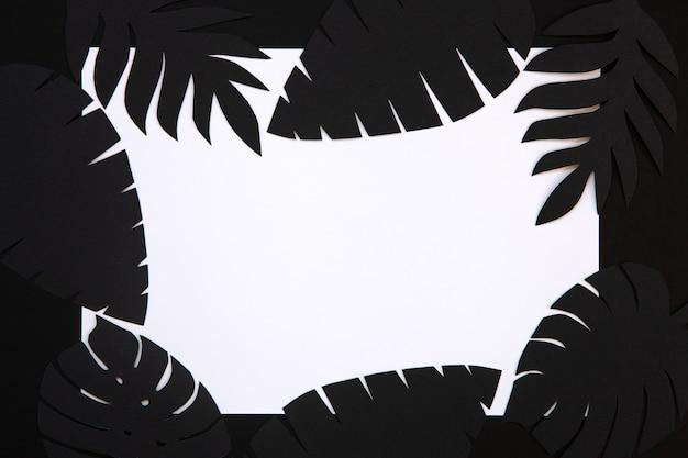 黒い紙のクローズアップ写真現実的な熱帯植物は白い背景の形の紙カット装飾を残します