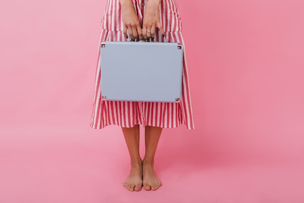 ミディアム丈のドレスを着たスリムな女の子の手に青いブリーフケースのクローズアップ写真。