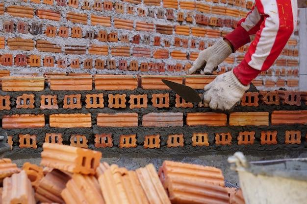 건설 현장에서 벽돌에 의해 벽돌공 노동자의 사진을 닫습니다.