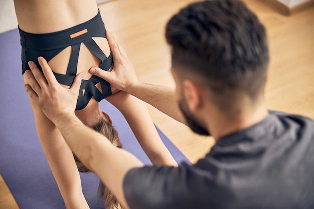 女性が正しく運動するのを助けるひげを持つブルネットの男性の写真を閉じる