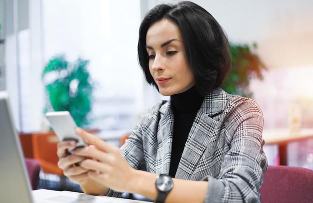 スマートフォンでメッセージを入力して笑っているスマートな服装のビジネスウーマンのクローズアップ写真。