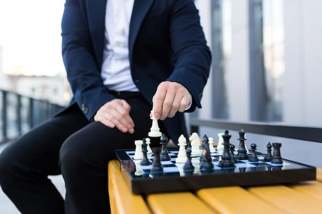 チェス盤で動きをしているビジネスマンの手のクローズアップ写真、チェスをしている男性のビジネスマン