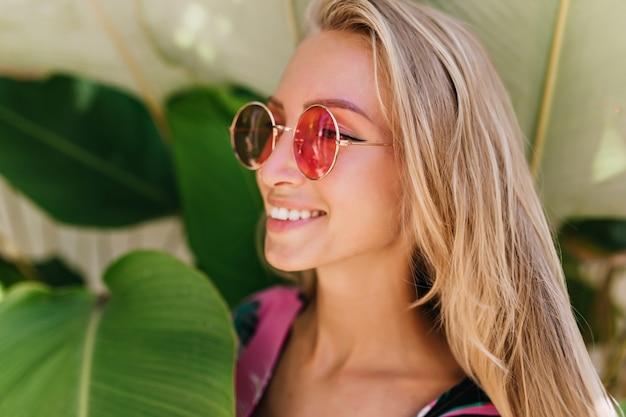 평온한 금발 여자의 근접 사진은 아름다운 분홍색 선글라스를 착용합니다.