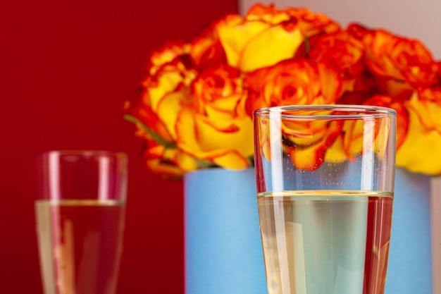 花瓶のバラとシャンパングラスの写真をクローズアップ