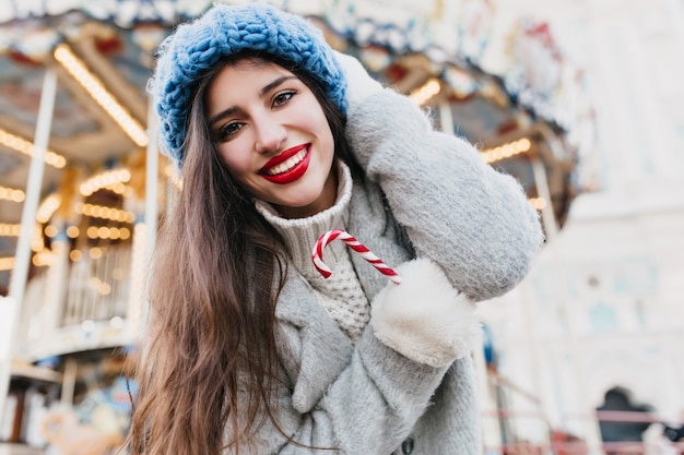 黒い髪と赤い唇のクリスマスロリポップで屋外のゾッと魅力的な女の子のクローズアップ写真。 12月の遊園地でポーズをとって青いニットベレー帽で笑っている若い女性の肖像画。