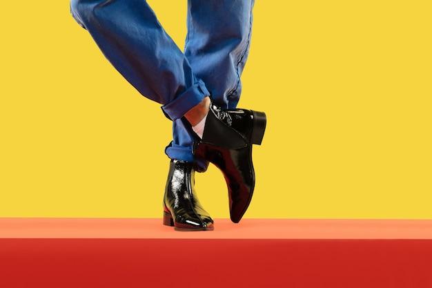 밝은 스튜디오 배경에 화려한 옷에 매력적인 남자의 사진을 닫습니다. 패션, 분위기, 스타일, 옷 개념. 청소년 문화, copyspace. 판매 또는 광고용