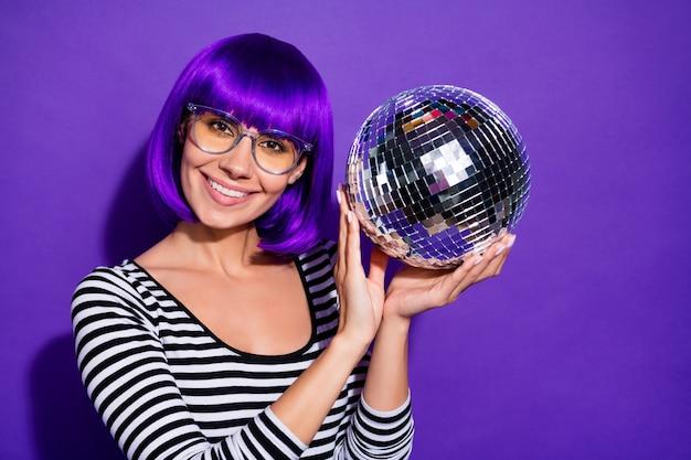 紫紫の背景の上に分離された魅力的なミレニアル世代の保持ミラーボールの摩耗仕様の写真を閉じる