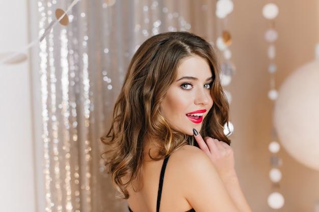 큰 파란 눈을 가진 매력적인 여자의 클로즈업 사진은 새해 파티에서 즐거운 시간을 보냅니다. 스파클 벽에 장난스럽게 포즈를 취하는 빨간 립스틱과 매력적인 아가씨의 실내 초상화.