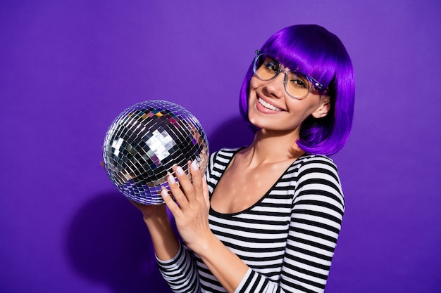Крупным планом фото очаровательной молодежи, держащей зеркальный шар, улыбающегося, изолированного на фиолетово-фиолетовом фоне