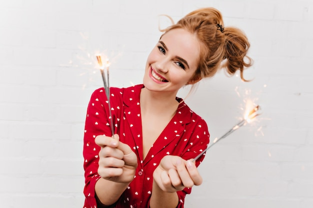 ベンガルライトを保持している陽気な白人の女の子のクローズアップ写真。線香花火と白い壁に分離された赤いパジャマの幸せな若い女性の肖像画。