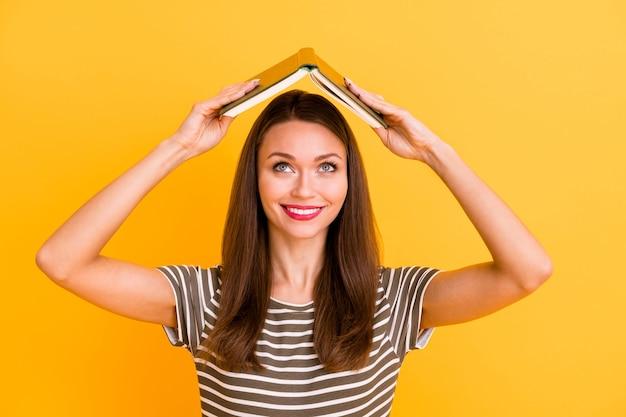 陽気な大学生の女の子のクローズアップ写真は頭の上に彼女の教科書を置きます勉強の後に楽しんでください自由な時間の休憩は格好良い服を着てください赤いポマード孤立した黄色の色の壁