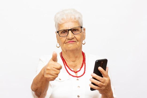 陽気な自信を持って興奮した夢のようなウェーブのかかった髪の老婆の女性が自画像を孤立した灰色の背景を作るの写真をクローズアップ