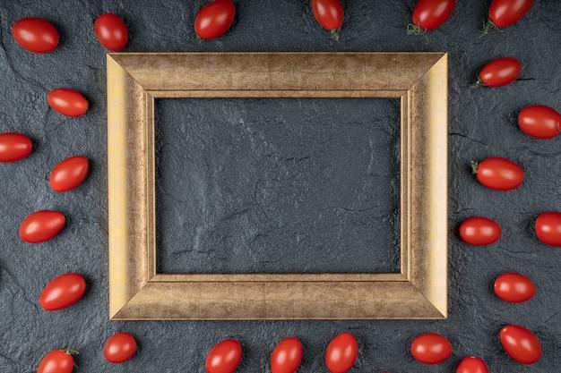Закройте фото помидоров черри вокруг золотой рамки на черном фоне. фото высокого качества