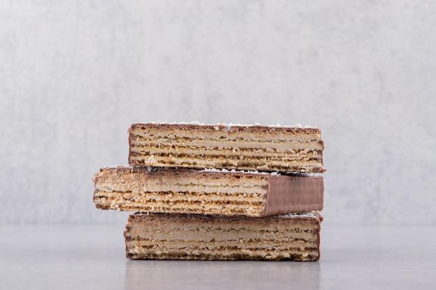 회색 배경에 초콜릿 웨이퍼 스택의 사진을 닫습니다.
