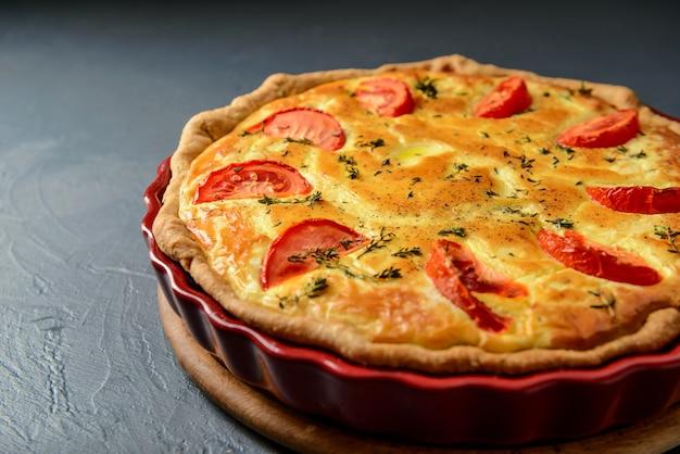 トマトと古典的なキッシュロレーヌパイのクローズアップ写真