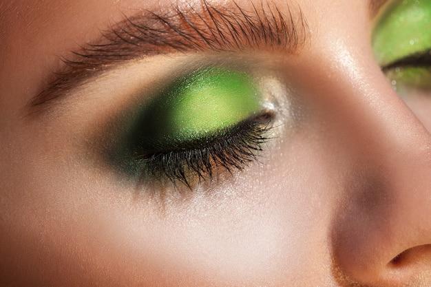 Крупным планом фото закрытых глаз с зеленым макияжем