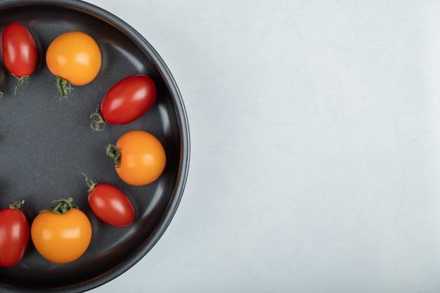 白い背景の上の鍋にカラフルなチェリートマトの写真を閉じます。高品質の写真