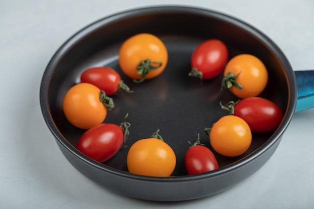 白い背景の上の鍋にカラフルな新鮮なチェリートマトの写真を閉じます。高品質の写真