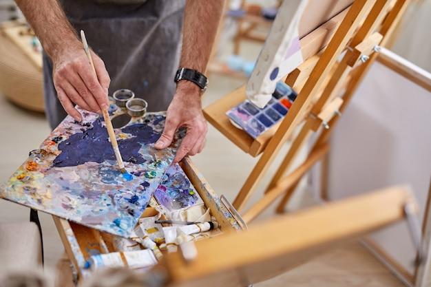 アートスタジオのカラフルなペイントパレットのクローズアップ写真、キャンバスに描画するためのアーティストの混合ペイント