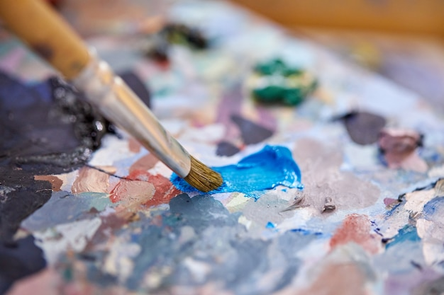 아트 스튜디오에서 다채로운 페인트 팔레트의 근접 사진, 아티스트 혼합 페인트 캔버스에 그리기