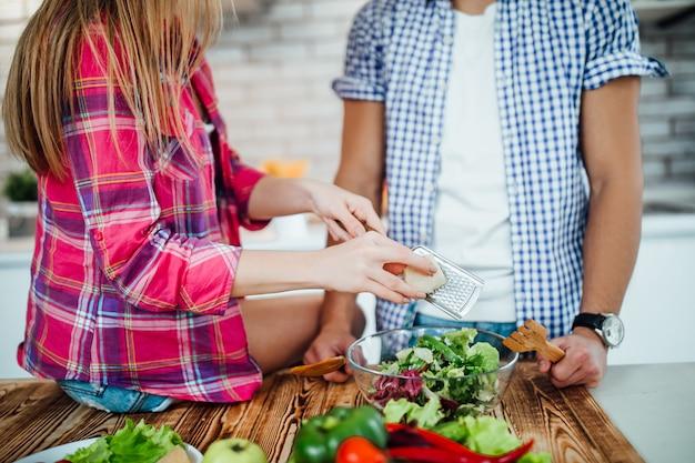 Крупным планом фото пара делает овощной завтрак, женщина руки, держа терку