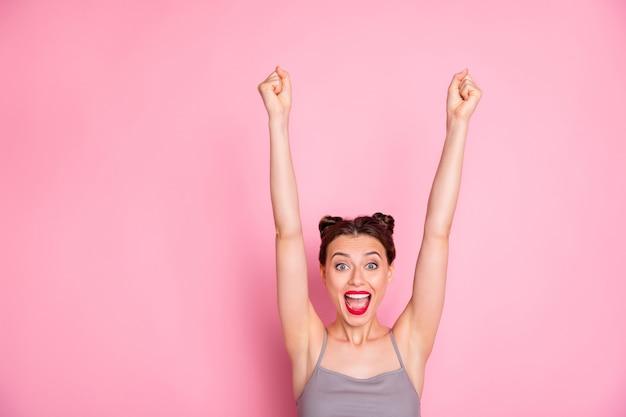 クレイジーな熱狂的な女の子のクローズアップ写真が望ましいプレゼントギフトを獲得驚きの悲鳴を上げる叫び拳を上げるピンク色で隔離された格好良い服を着る