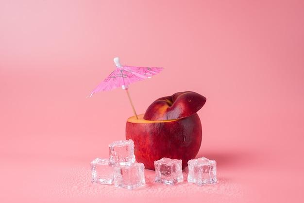 その中にカクテル傘とコピースペースでピンクの背景に分離された氷を溶かしているカットリンゴのクローズアップ写真