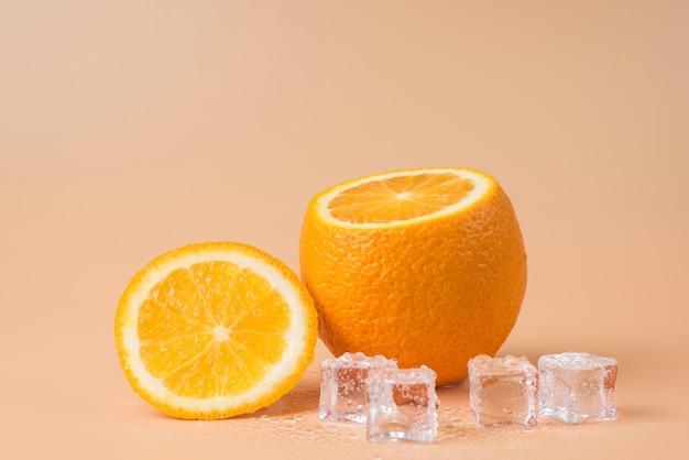 砂浜の背景に分離されたカットオレンジと溶ける角氷のクローズアップ写真