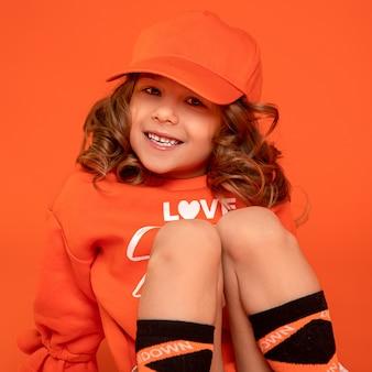 オレンジ色の背景に膝を抱いて、6〜7歳のかわいい美しい女の赤ちゃんのクローズアップ写真。モックアップ用のキャップ。歯を見せる笑顔