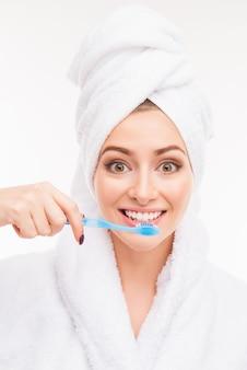 歯ブラシを保持している彼女の頭にタオルでかわいい女の子の写真を閉じる