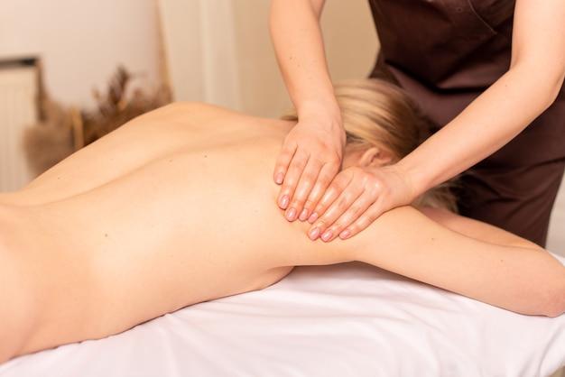 Крупным планом фото массажа глубоких тканей. массажистка делает массаж плеч и спины