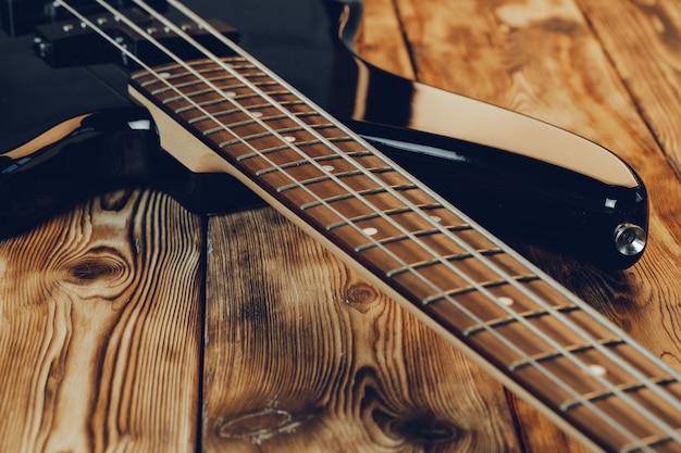 暗い背景上のエレクトリックギターの指板の写真をクローズアップ