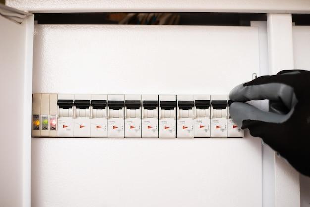 Крупным планом фото рук электрика в перчатках проверяет электрическую панель с предохранителями