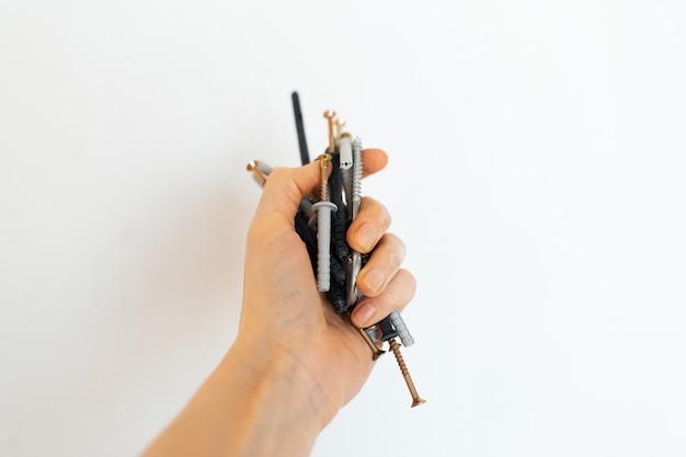 셀프 태핑 나사를 들고 있는 여성 손의 클로즈업 사진.