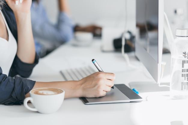 タブレットでスタイラスを持っている女性の手のクローズアップ写真。オフィスでのコーヒーブレイク中にプロジェクトに取り組んでいるフリーランスのウェブ開発者の屋内の肖像画。