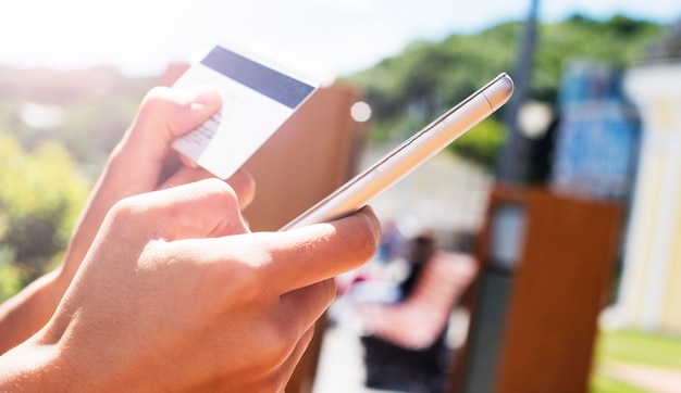 オンラインショッピングのためにスマートフォンとクレジットカードを使用して女性の手の写真を閉じる