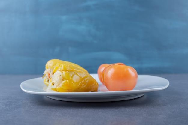 하얀 접시에 빨간 토마토와 채워진된 피망의 사진을 닫습니다.