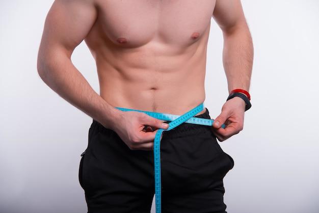 Крупным планом фото фитнес-мужчина, измерения абс с лентой