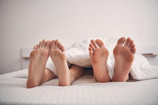 사랑하는 부부에 속하는 침대에서 네 다리의 사진을 닫습니다