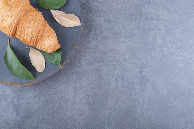 灰色の木の板にフランスのクロワッサンの写真をクローズアップ。