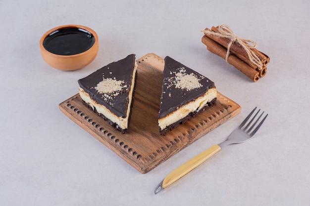 シナモンと灰色の上のフォークで新鮮なチョコレートケーキのスライスの写真を閉じる