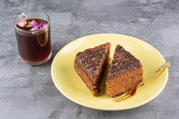 노란색 접시에 신선한 초콜릿 조각과 회색에 차 한잔의 사진을 닫습니다.