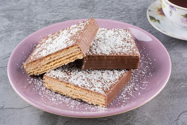 보라색 접시에 신선한 초콜릿 웨이퍼의 사진을 닫습니다.