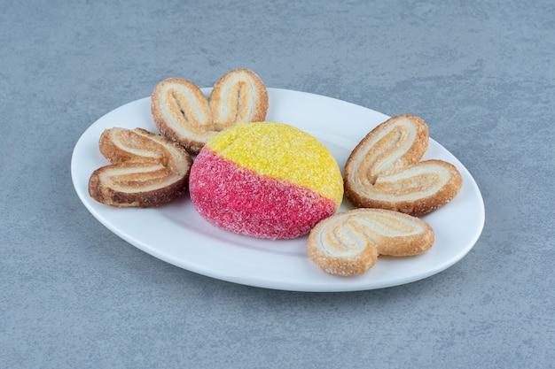 회색 배경에 흰색 접시에 신선한 쿠키의 사진을 닫습니다.