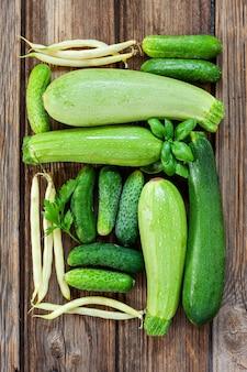 新鮮な農場の有機緑野菜と緑のクローズアップ写真。木製の背景の上面図