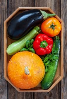 新鮮な農場の有機野菜と緑のクローズアップ写真。木製の背景の上面図